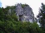 Urcand pe drumul forestier, din padure se ivesc primele stanci ale cheii Valea Seaca.